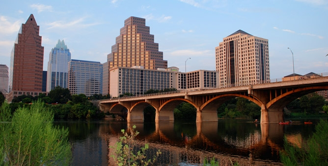 City of Austin Login Image: City buildings, bridge reflecting in water